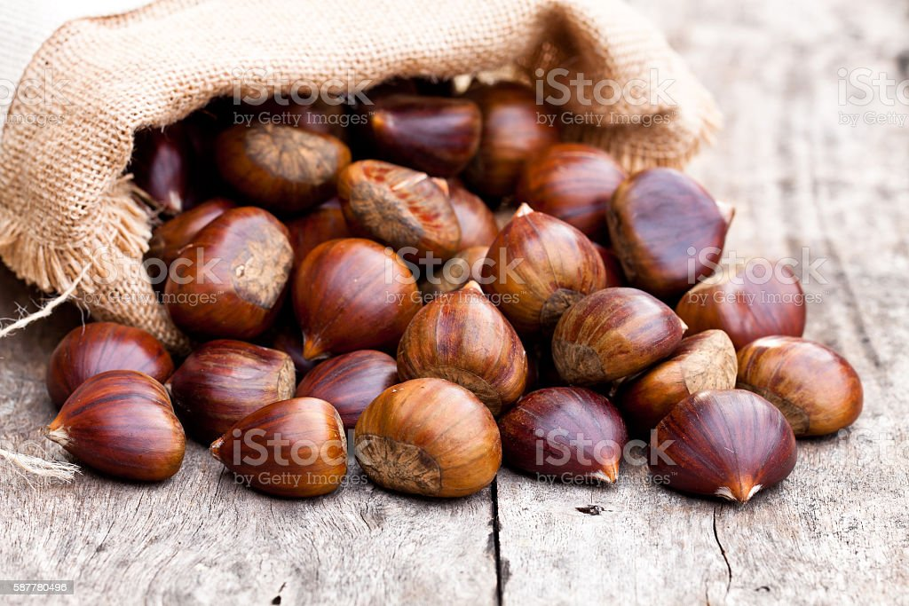 fresh  chestnuts in sack bag on the old wooden table stock photo
