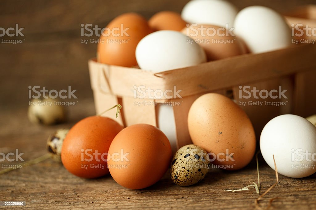 Fresh chicken and quail eggs on a wooden background stock photo
