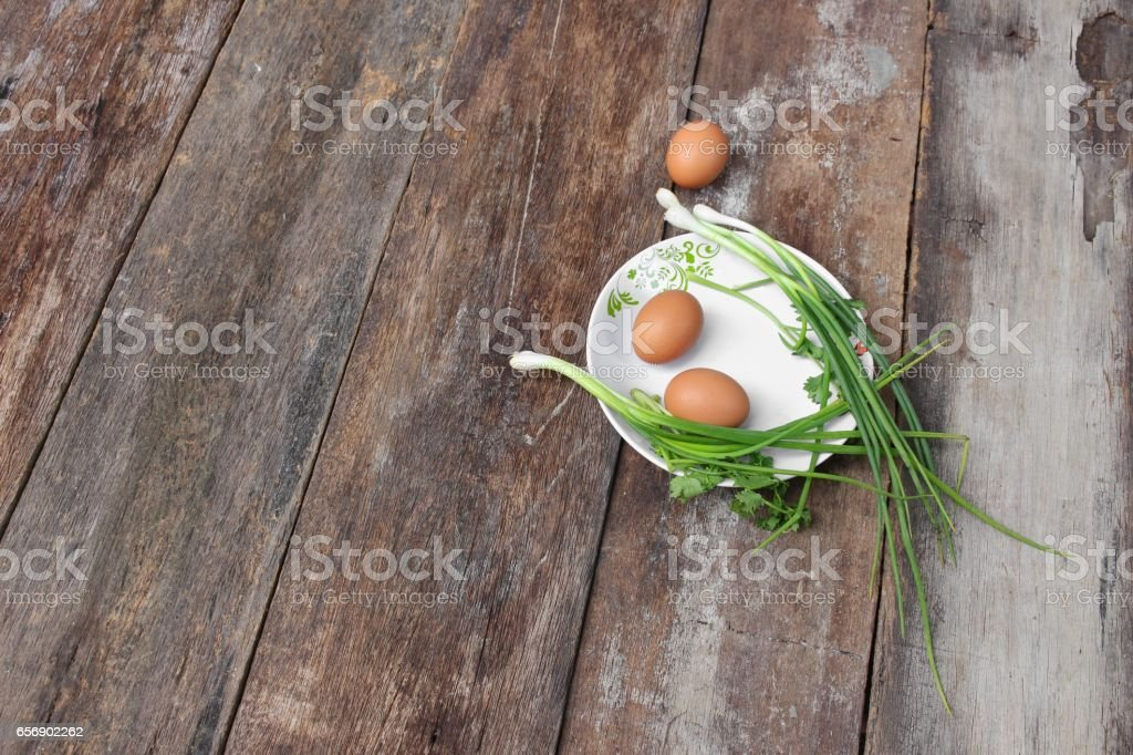 fresh chicken egg on a plate Close up and onion in wooden stock photo