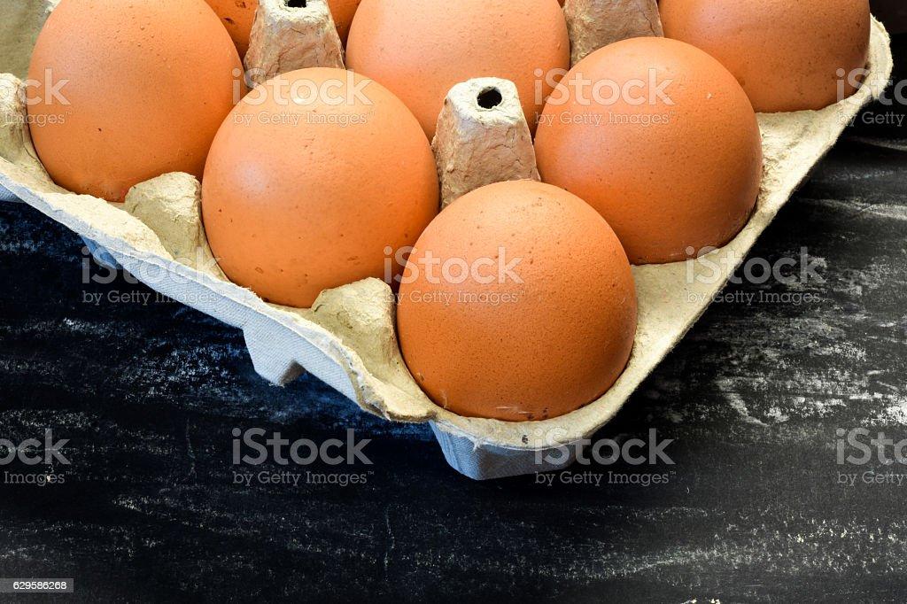 Fresh chicken eggs in box. Black background. stock photo