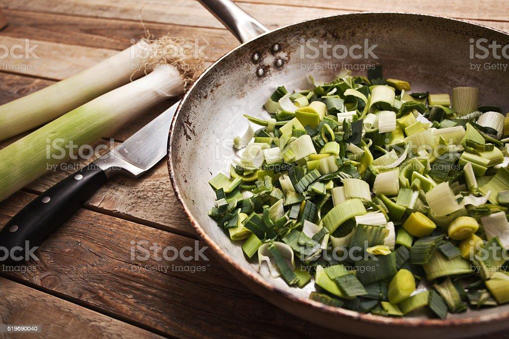 Fresh chopped leek in frying pan stock photo