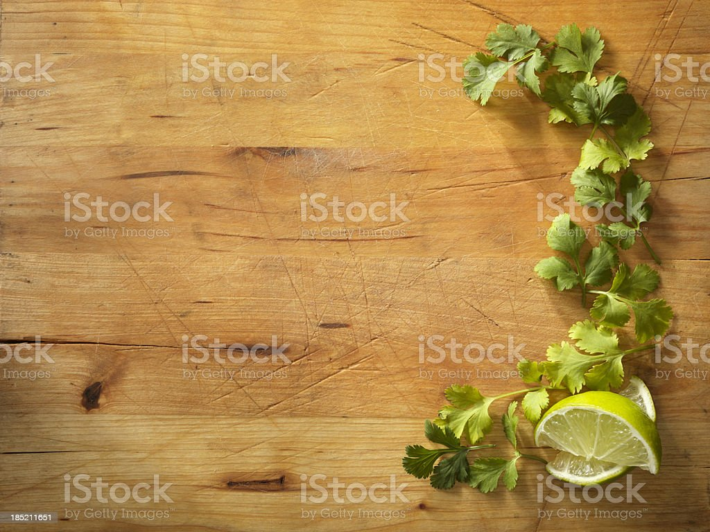 Fresh cilantro and lime on wooden cutting board royalty-free stock photo