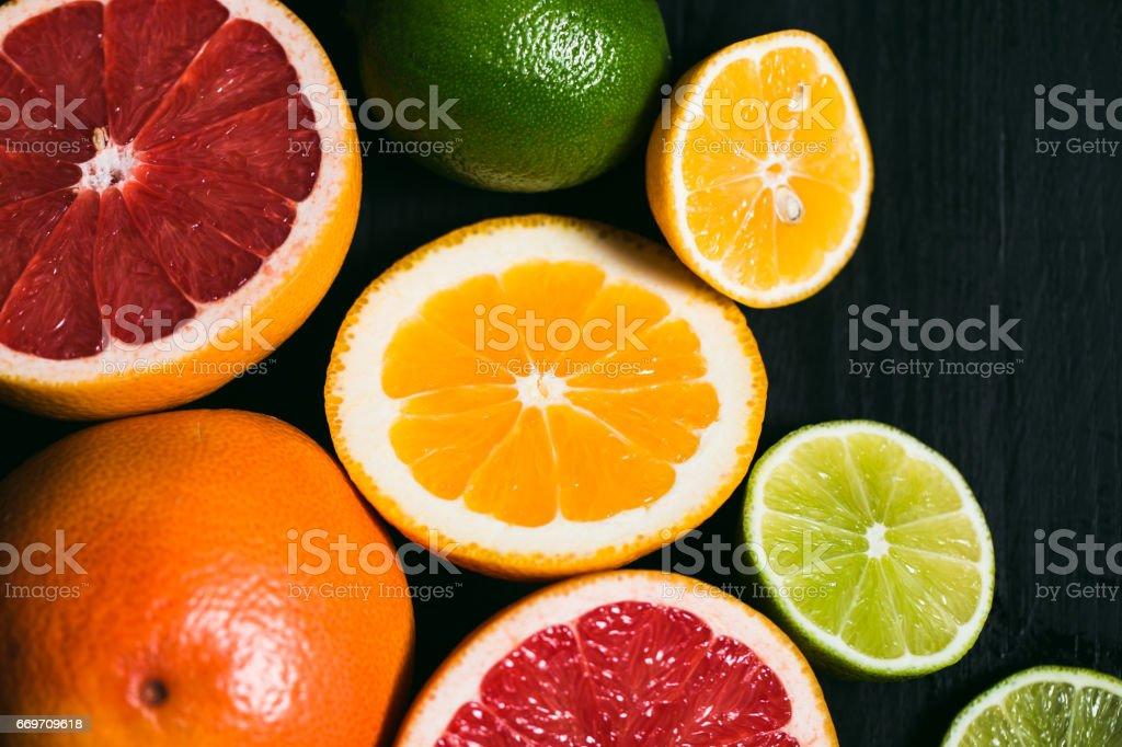 Fresh citrus stihli. Lemons, limes, grapefruit and orange on a black...