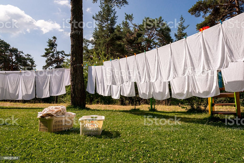 fresh clean white towels drying on washing line in outdoor stock photo