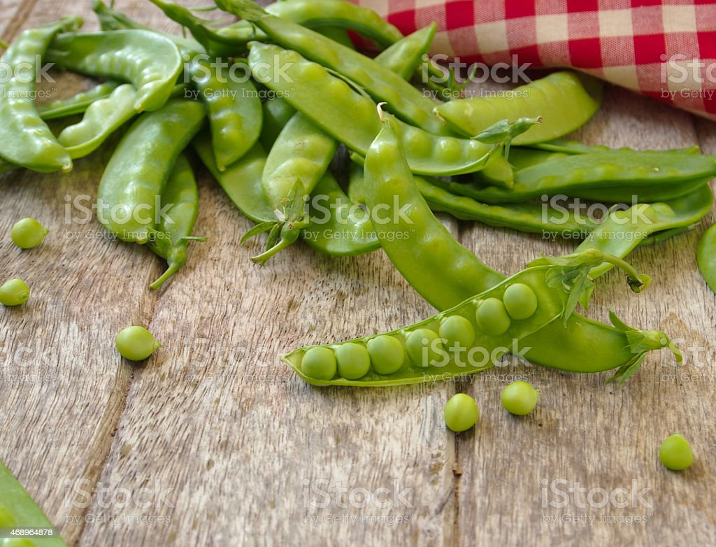 Fresh closed peas with one pod open stock photo