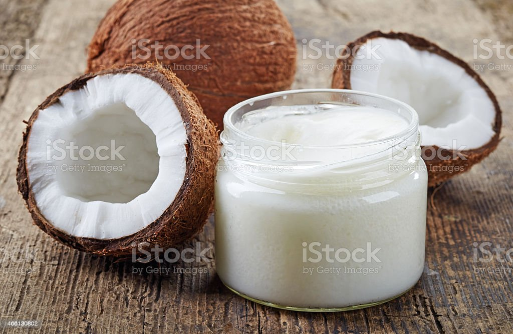 Fresh coconuts and a jar of coconut oil on a wooden table stock photo