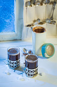 Fresh coffee pot and cup with spoons by frozen window