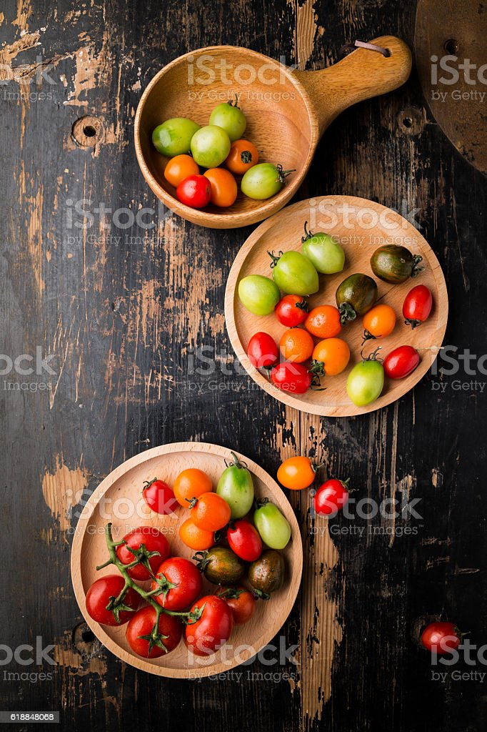 Fresh Colorful tomatoes on wooden table stock photo