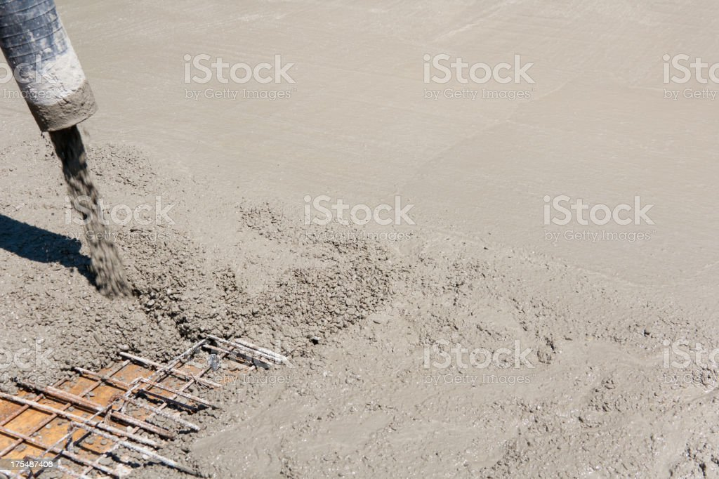 Fresh concrete being poured into a metal grating stock photo