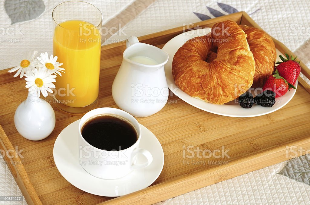 Fresh continental breakfast on a wooden tray on a bed stock photo
