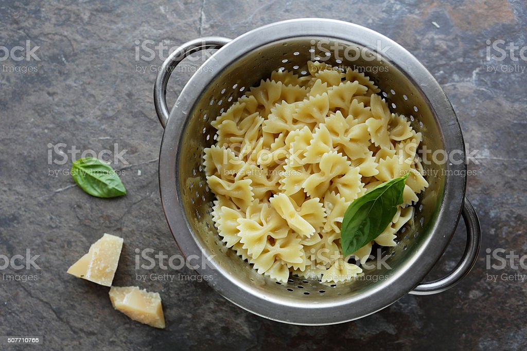 fresh cooked pasta in colander stock photo