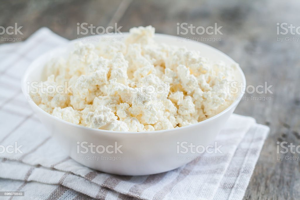 fresh cottage cheese in a white bowl on  wooden background stock photo