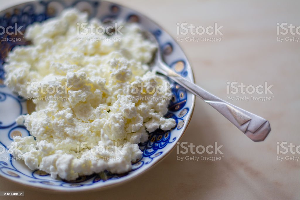 fresh cottage cheese on old wooden table stock photo