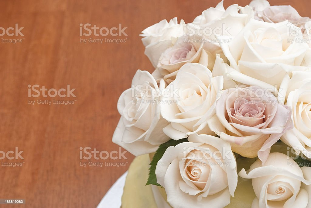Fresh cream and Latte roses on a wedding cake stock photo