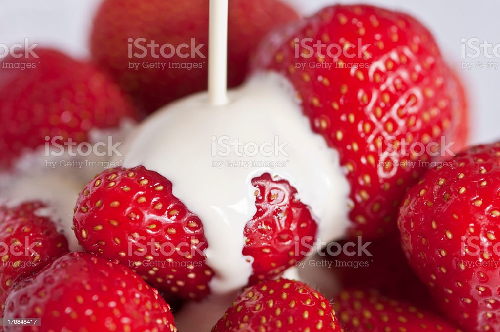 Fresh cream being poured over fresh strawberries stock photo