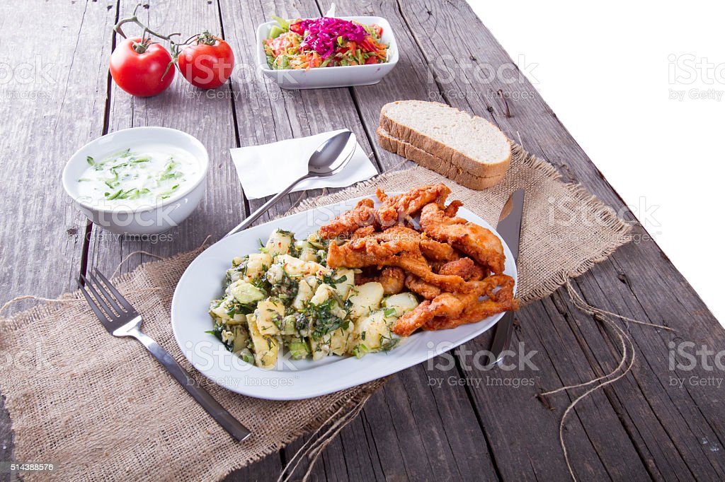 fresh, crispy fried chicken and potato salad on wooden table stock photo