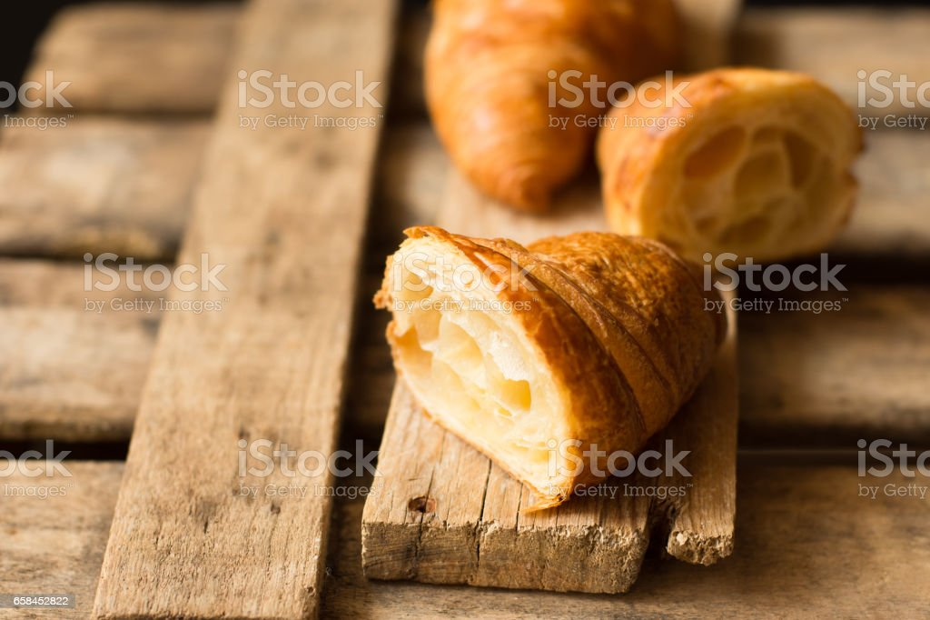 Fresh croissant cut in half with flaky pastry inside visible, on aged wood background,close up,kinfolk stock photo
