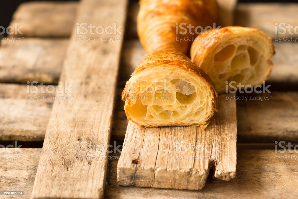 Fresh croissant cut in half with flaky pastry inside visible, on wood background,close up,kinfolk stock photo