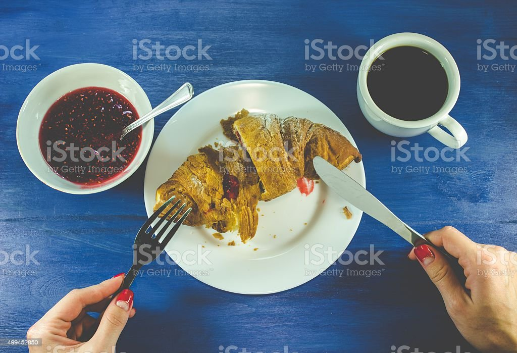 Fresh croissant with jam and coffee on wooden table stock photo