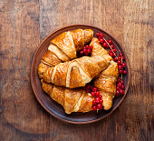 fresh Croissants with Berries on a vintage wooden table.