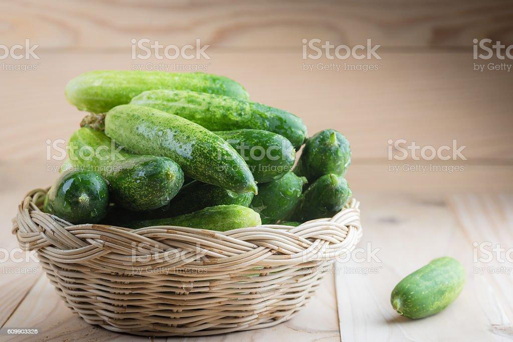Fresh cucumbers in basket on wood stock photo