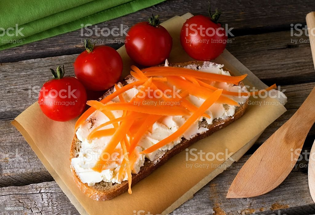 Fresh curd cheese on bread with carrot stock photo