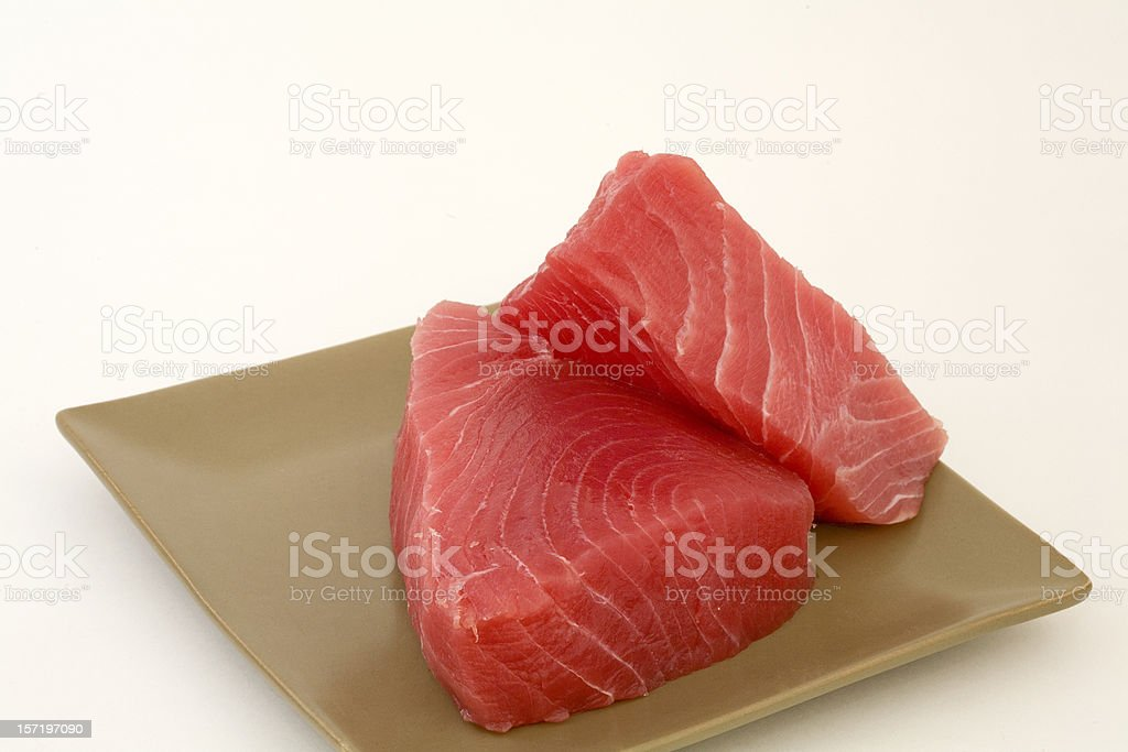 Fresh cut Ahi on a square tan plate ready to cook royalty-free stock photo