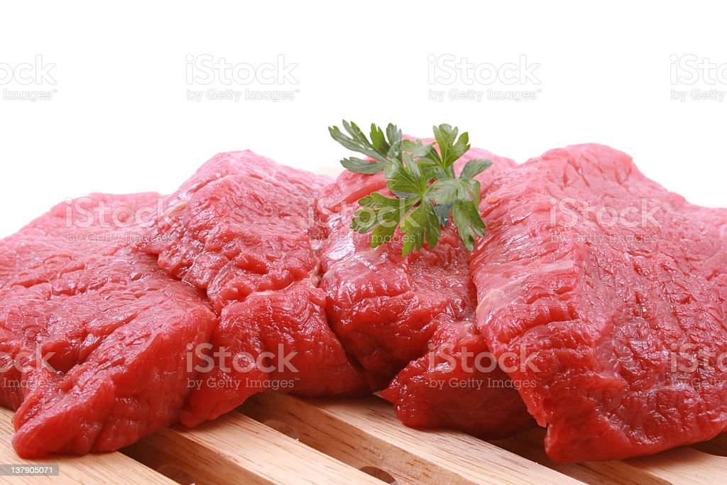 Fresh cuts of beefs garnished with herb on wooden grates royalty-free stock photo