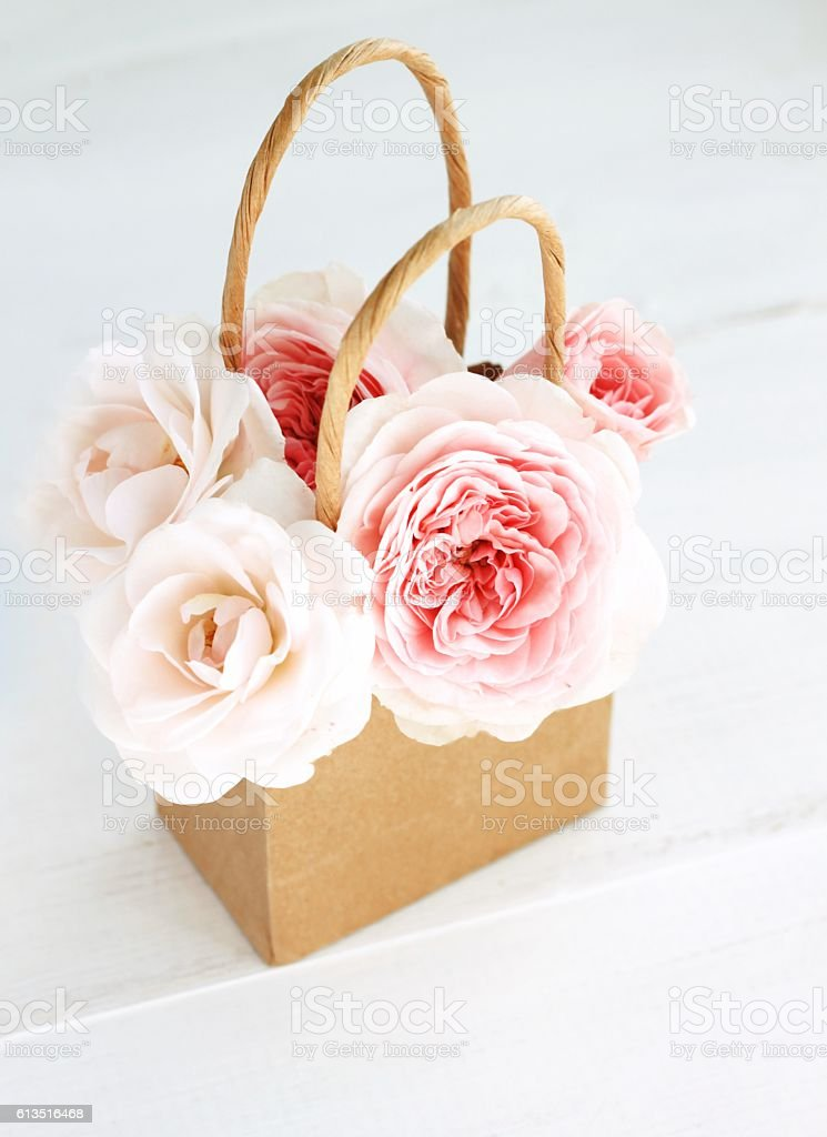 Fresh delicate roses in craft paper shopping bag. stock photo