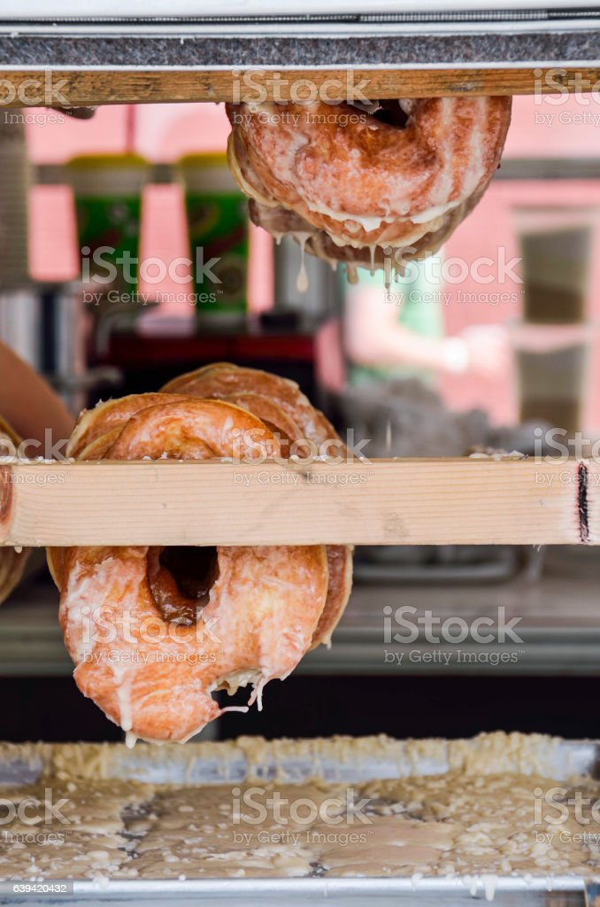 Fresh donuts hanging with icing dripping down stock photo