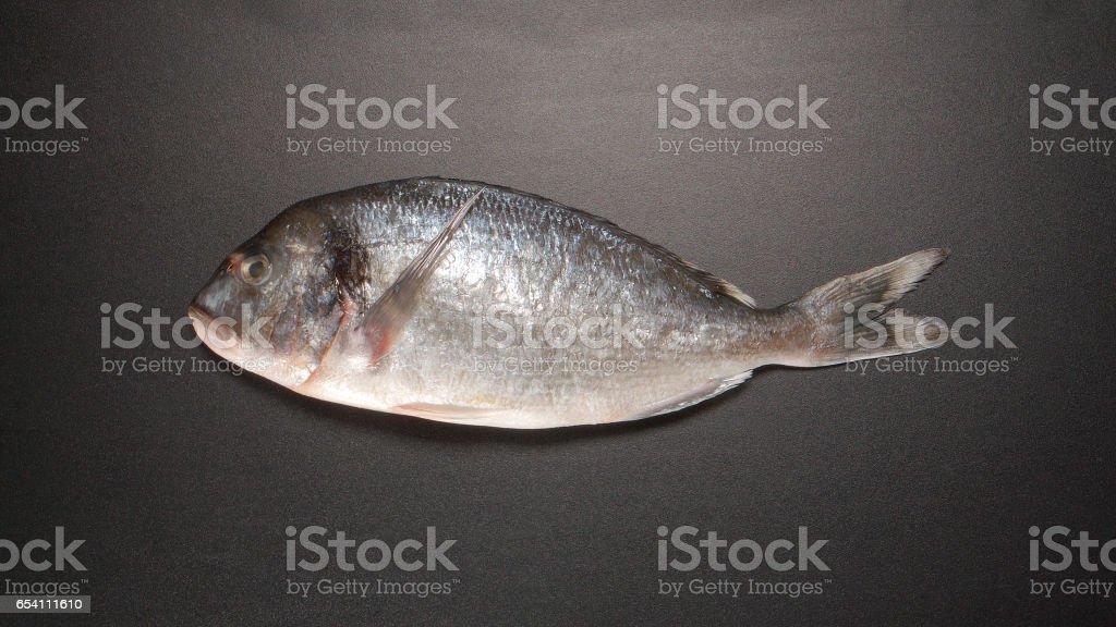 TOP VIEW: Fresh Dorade fish on black table stock photo