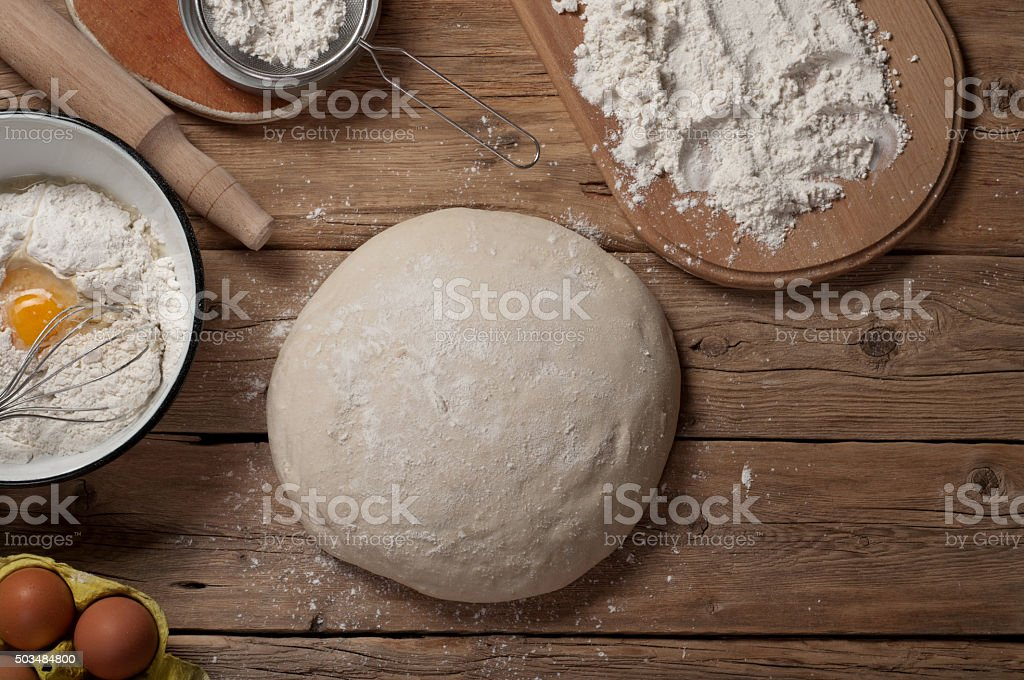 Fresh dough on a wooden table in a bakery stock photo
