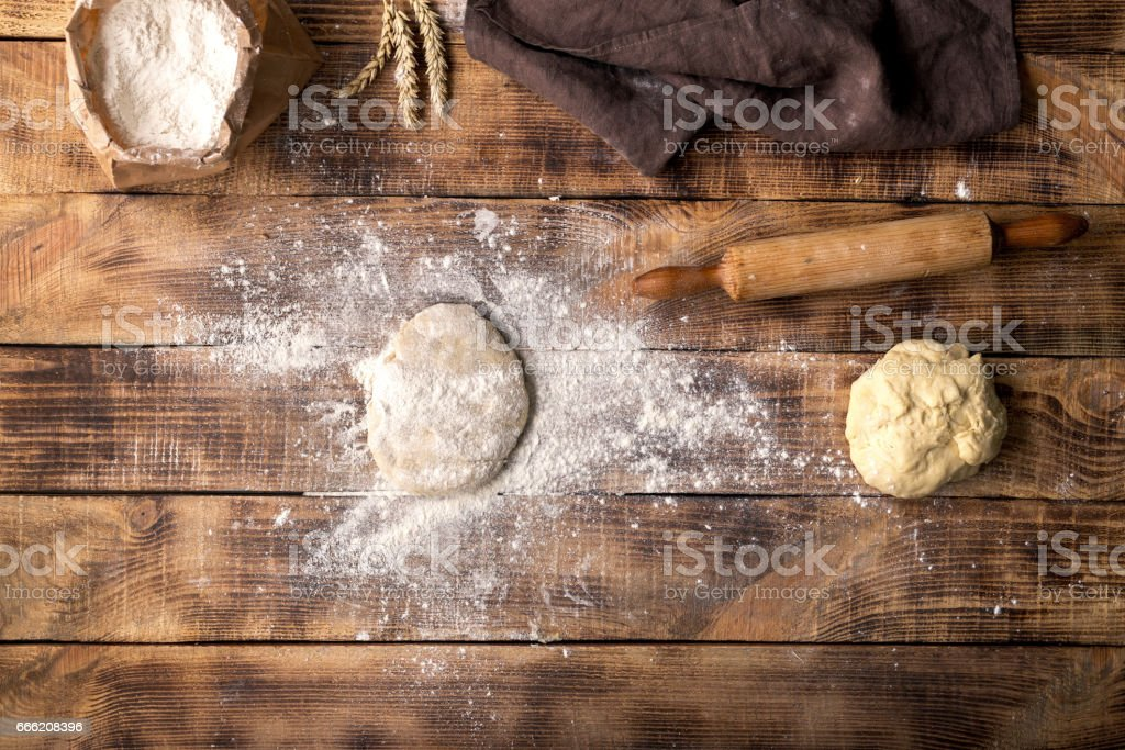 Fresh dough sprinkled with flour on a wooden table stock photo
