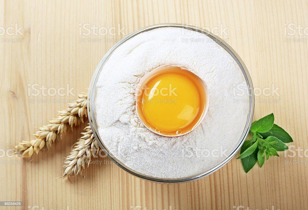 Свежие яйца в миску муки Стоковые фото Стоковая фотография