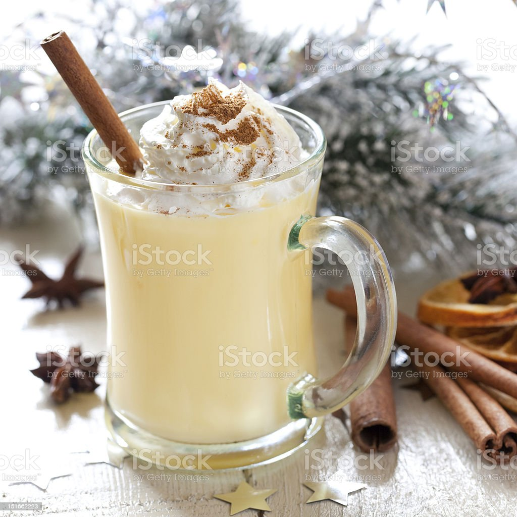 Fresh eggnog in a glass mug with wintry branches and spices royalty-free stock photo