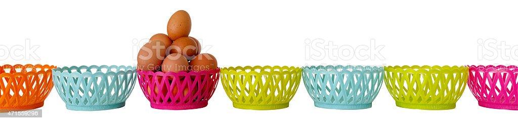 Fresh eggs in a basket amongst many empty baskets. stock photo