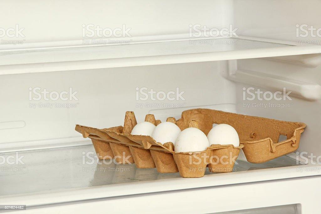 Fresh eggs in a paper box on refrigerator shelf. stock photo
