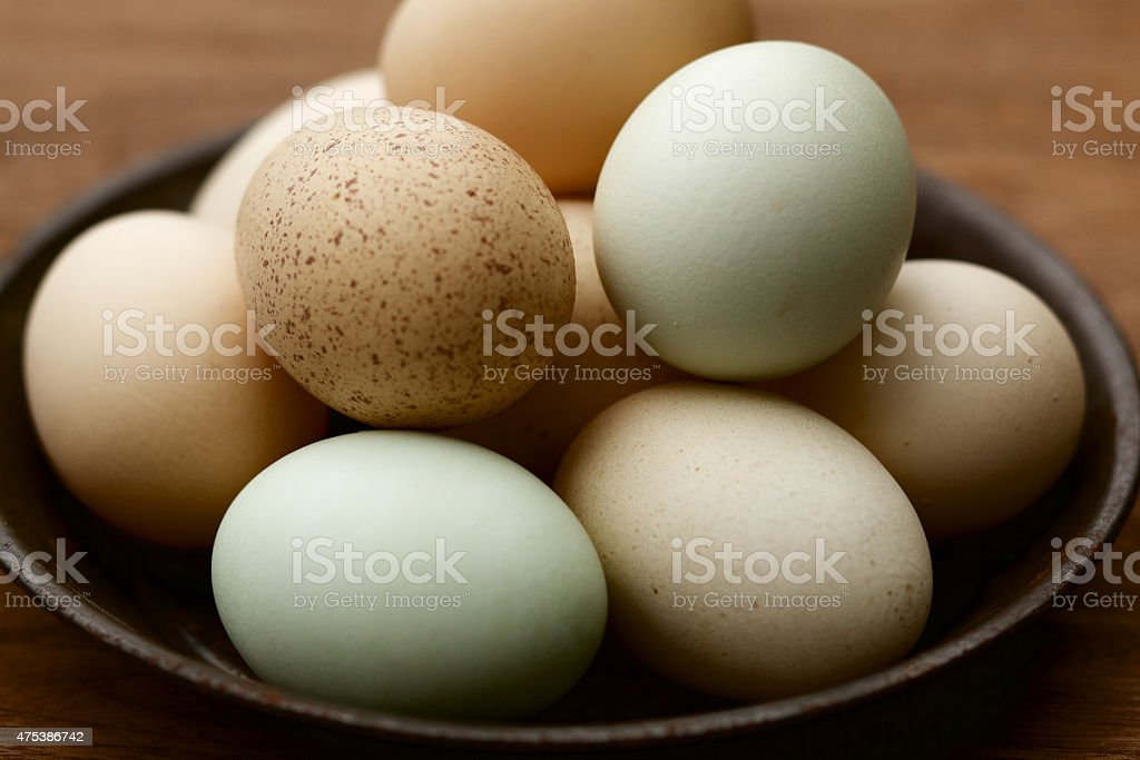 Fresh eggs in rusted metal bowl stock photo