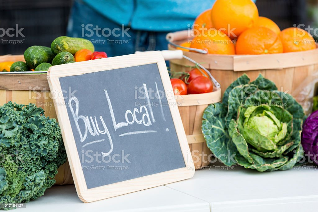 Fresh farmers market veggies with buy local chalkboard sign stock photo