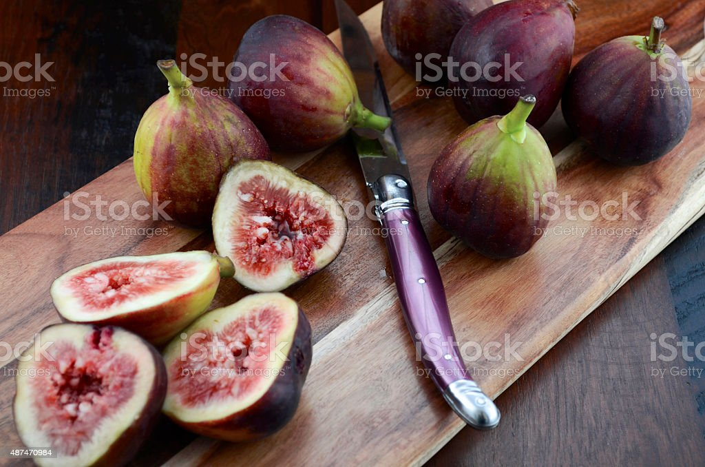 Fresh figs on wooden cutting board with knife. stock photo