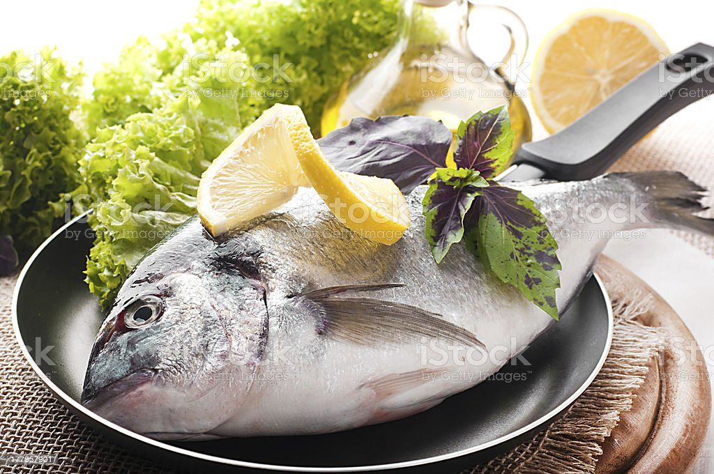 Fresh fish of dorado on a frying pan royalty-free stock photo