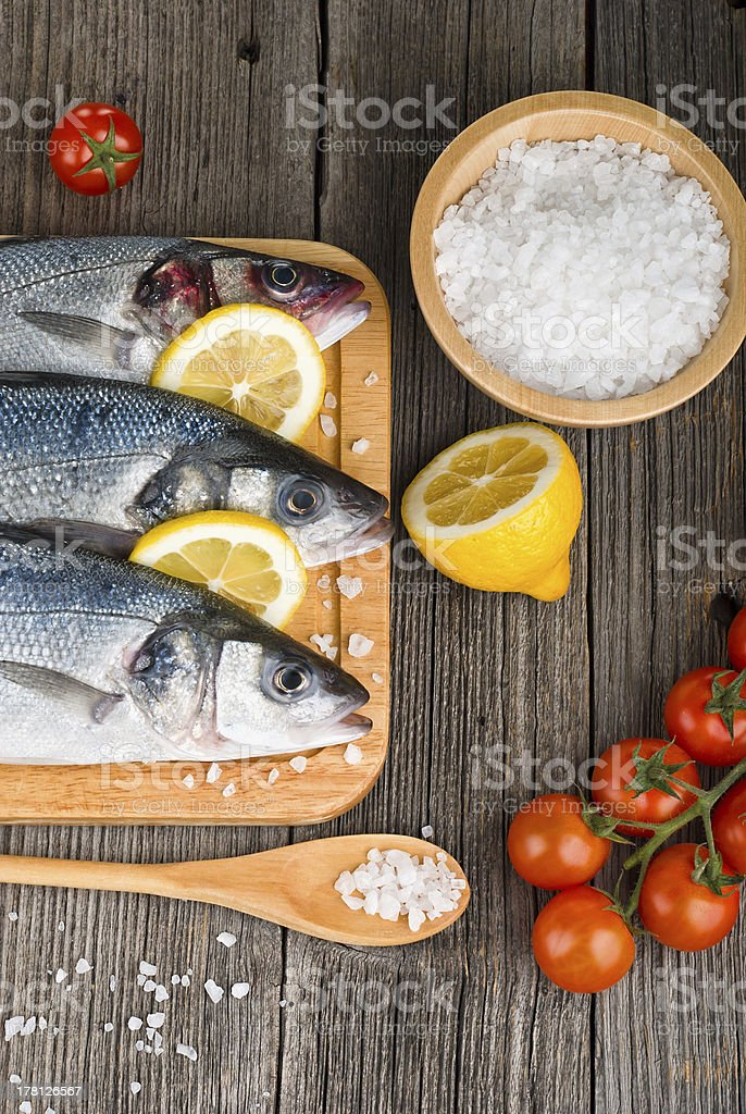 Fresh fish on chopping board with salt stock photo