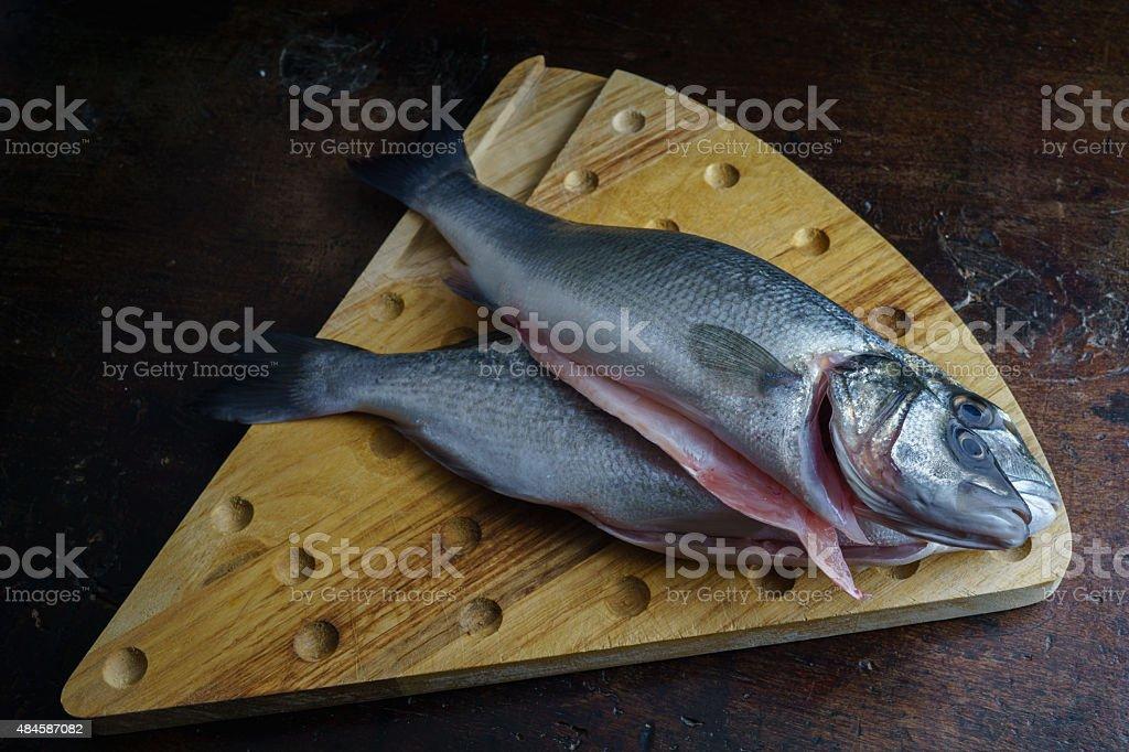 fresh fish on cutting board bream and sea bass stock photo
