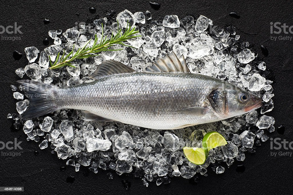 Fresh fish on ice on a black stone table stock photo