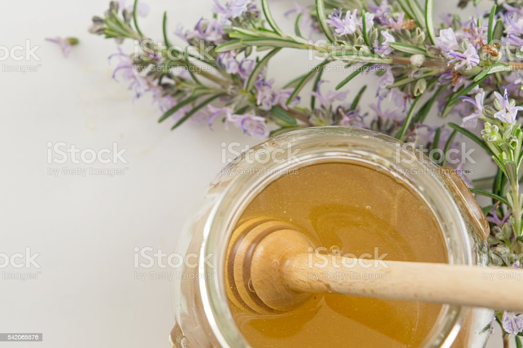 Fresh flowers and a jar of honey stock photo