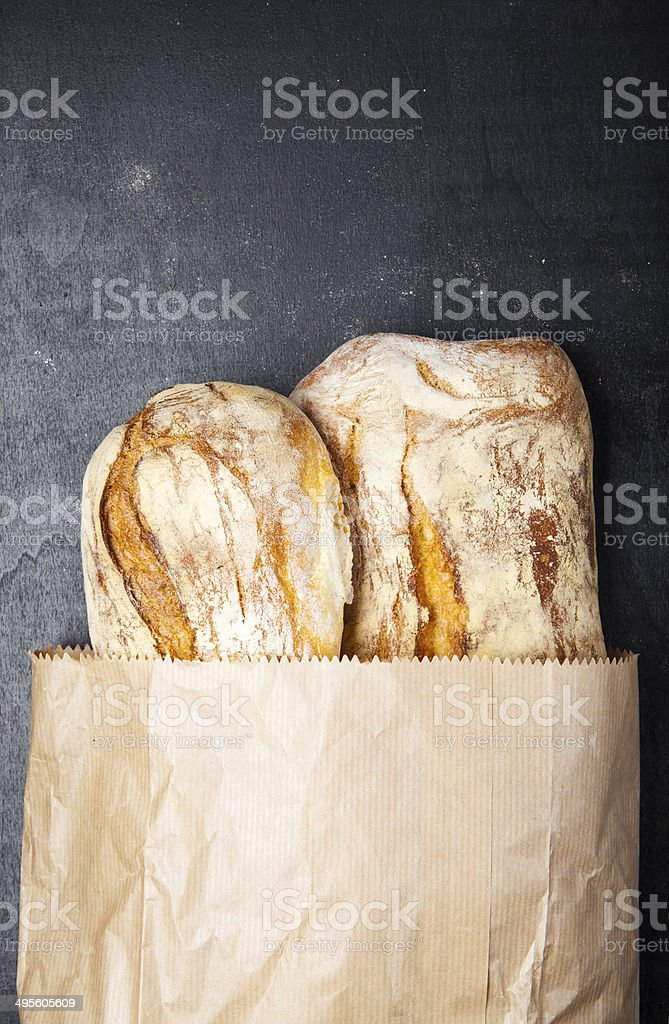 Fresh French cracked bread paper bag on a dark background stock photo
