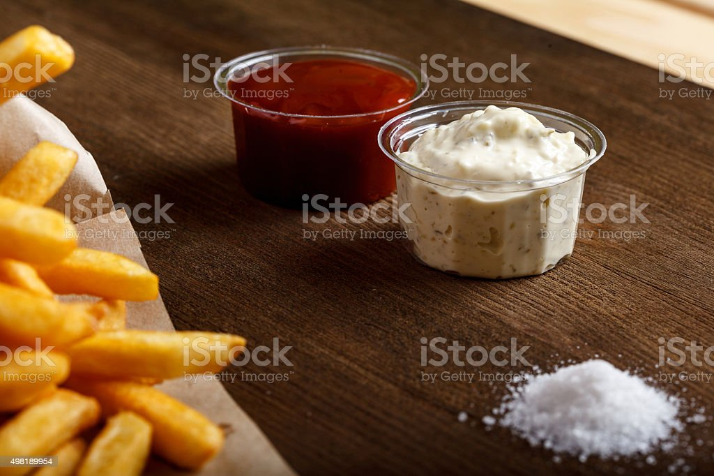 Fresh fried french fries with ketchup on wooden background stock photo