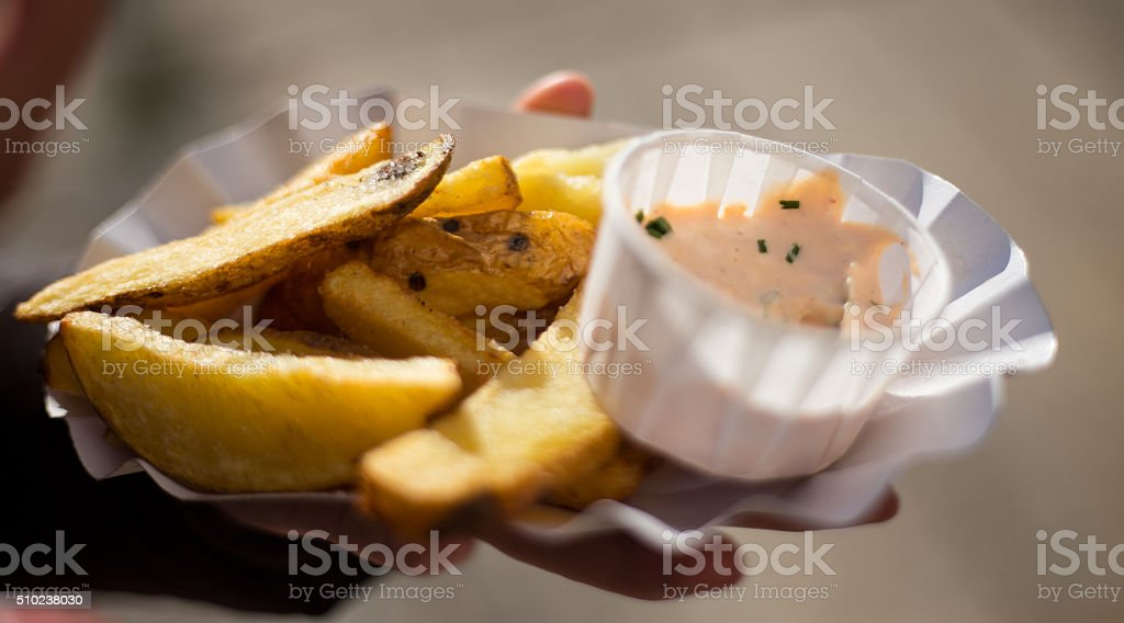 Fresh fried potato with dressing holded by woman hands stock photo