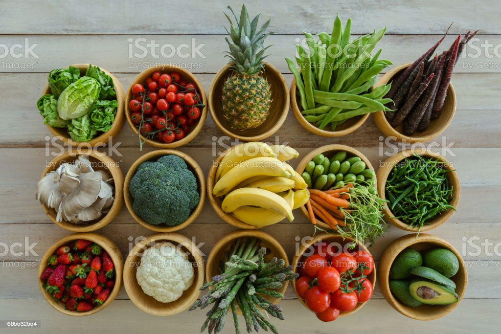 Fresh fruit and vegetable variety over wooden backdrop stock photo