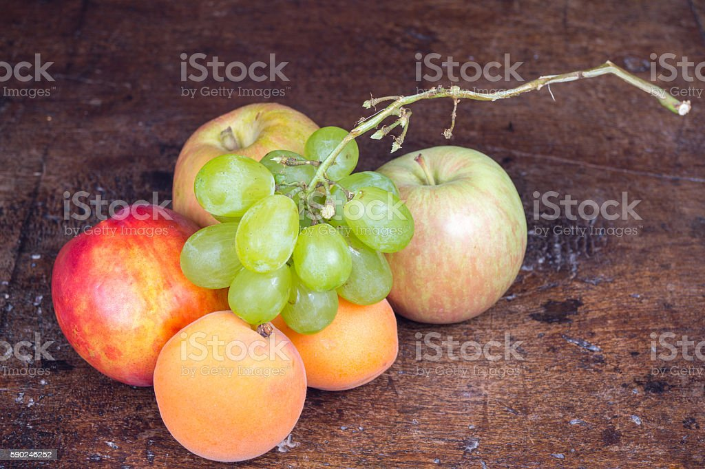 fresh fruit in the foreground on antique table stock photo